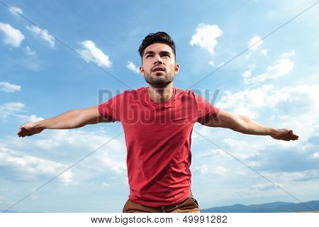 casual young man outdoor with arms like wings preparing to fly while looking away
