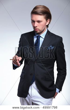 young business man looking down while holding a hand in his pocket and a cigarette in the other. on a gray background