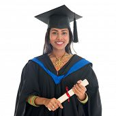 Happy Indian university student in graduation gown and cap holding diploma certificate. Portrait of