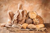 stock photo of whole-grain  - Various kind of bread on wooden surface - JPG