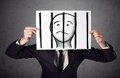 stock photo of faceless  - Businessman holding a paper with a prisoner in jail behind the bars on it in front of his head - JPG