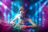picture of disc jockey  - Pretty Dj mixing music in a club with blue and purple lights - JPG