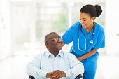 stock photo of nurse practitioner  - beautiful african nurse taking care of senior patient in wheelchair - JPG