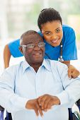 image of wheelchair  - elderly african american man and caring young caregiver at home - JPG