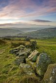 stock photo of wispy  - A classic Yorkshire dry stone wall leading the eye down towards the calder valley at sunset in autumn - JPG