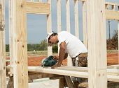 stock photo of wood pieces  - Framer building the wood structure of a new house is sawing a piece of lumber - JPG