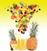Diffferent fruits and berries falls into glass of fresh juice, on yellow background