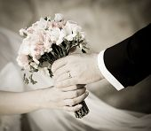 stock photo of married  - Groom handing wedding bouquet to bride - JPG
