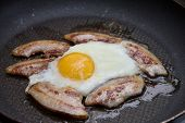 Bacon And Eggs Cooking In A Skillet
