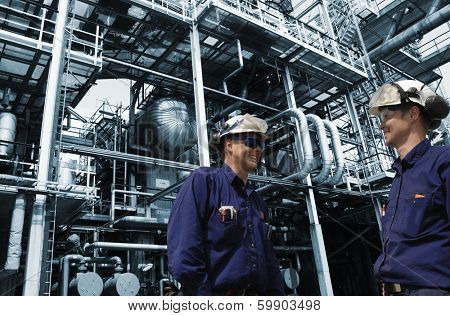 oil and gas engineers with details of pipelines and constructions, blue toned background