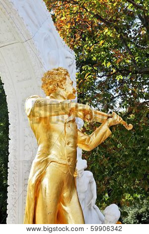 Park in Vienna.  Elegant gilded statue of Johann Strauss, playing the violin in white marble arch