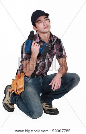 Pensive builder holding drill