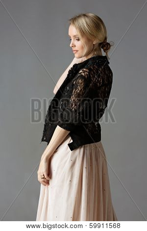 beautiful young blond woman with messy hair in a bun in a black lace jacket and pastel beige dress on studio background