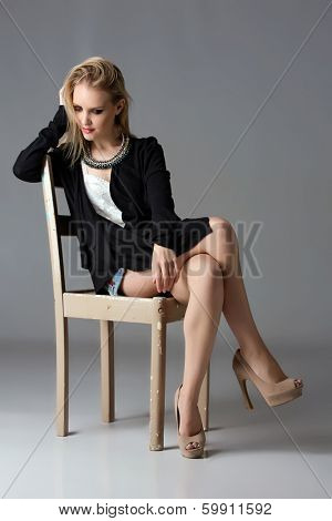 Beautiful blond woman wearing black cardigan, jean shorts and high heel shoes on grey studio background sitting on a rustic chair