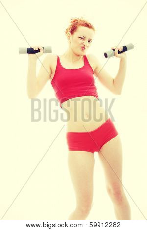 Beautiful, young, deaf (with hearing aid in ears) redhead exercising with dumb bells
