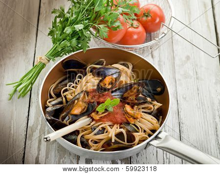spaghetti with mussels and tomato sauce over casserole