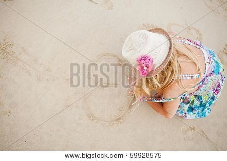 Young Girl Drawing Heart Shapes In Sand