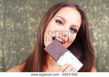Portrait of beautiful young girl with chocolate on shiny background