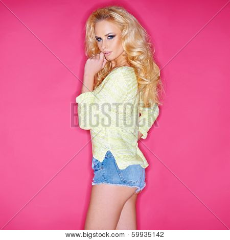 Beautiful blond woman in skimpy denim shorts standing sideways looking at the camera with a seductive expression   on pink