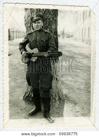 KURSK, USSR - CIRCA 1960s: An antique photo shows portrait of a Red Army soldiers with a guitar in his hands.