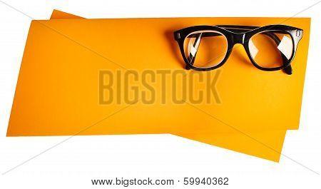 Vintage eyeglasses with black frame on orange creative  support.