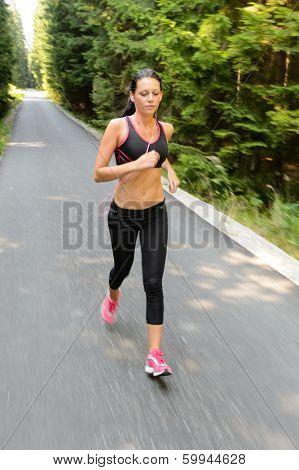 Runner - woman running outdoors training for marathon run motion blur