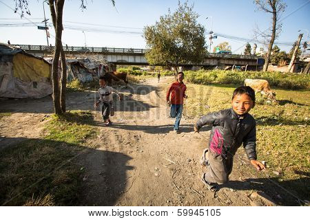 KATHMANDU, NEPAL - DEC 16, 2013: Unidentified poor children near their houses at slums in Tripureshwor district, Kathmandu. Caste of untouchables in Nepal, is about 7 % of population.