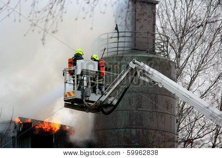 Firefighters Extinguishing Fire On Hydraulic Crane Platform