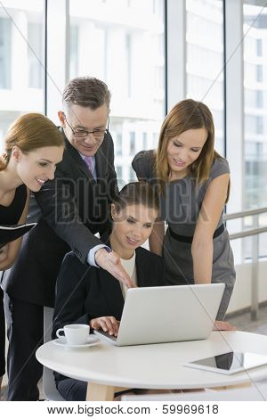 Business people working on laptop in office cafeteria