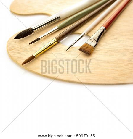 Art color brushes on wooden palette isolated on white background