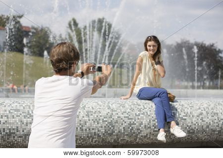 Rear view of man videotaping woman against fountain