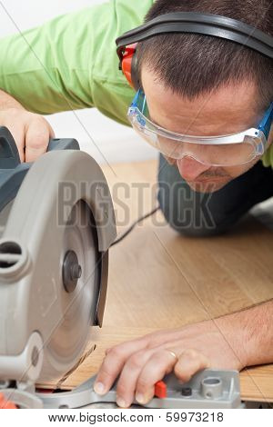 Man Cutting Laminate Floor Plank