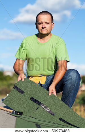 Worker Holding  Bitumen Roof Shingles On Top Of Building