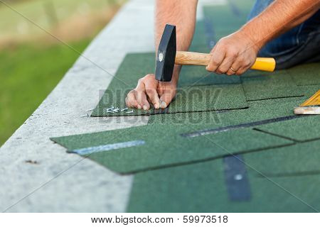 Worker Hands Installing Bitumen Roof Shingles