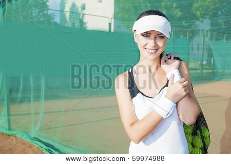 Happy And Positive Female Tennis Woman Holding Tennis Mesh Bag With Lots Of Balls