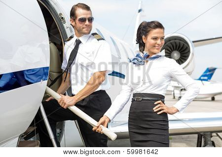 Beautiful airhostess with pilot boarding private jet