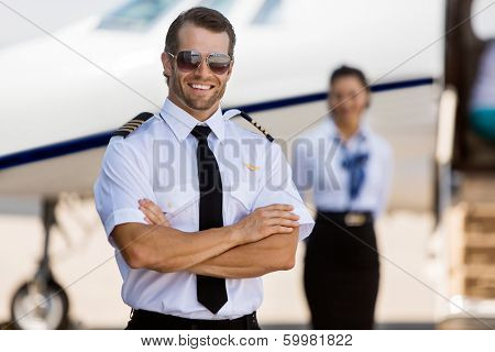 Portrait of confident pilot with arms crossed against stewardess and private jet at terminal