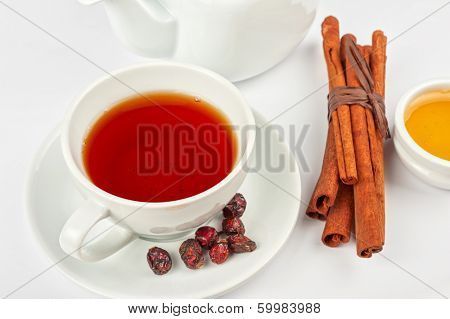 Cup of hot berries tea with cinnamon sticks, and honey