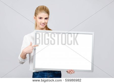 Young girl smiling and pointing to a white blank board
