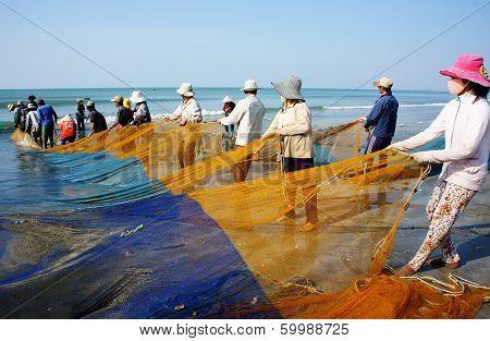 Group Of Fisherman Pull Fish Net