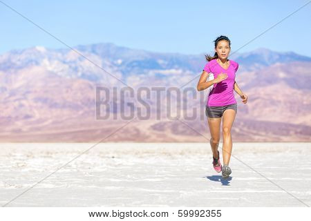 Running sport athlete woman sprinting in trail run in desert. Female fitness runner in sprint workout training in shorts and t-shirt. Fit muscular girl sport model outside under blue sky.