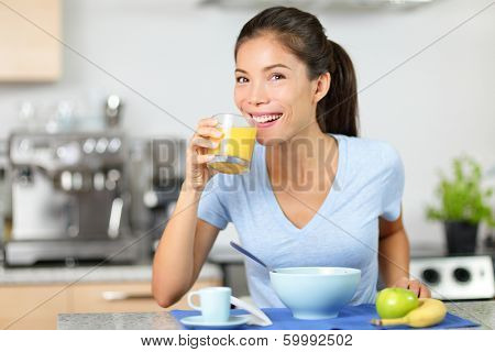 Woman drinking orange juice eating breakfast smiling happy in the morning. Beautiful young multiracial woman sitting in her kitchen at home. Mixed race Asian Caucasian female model eating healthy.