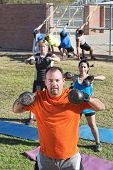 pic of boot camp  - Confident man and group lifting weights in boot camp fitness class