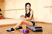 Young smiling fit woman sitting on the step board at gym