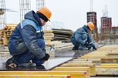 stock photo of concrete pouring  - construction worker at construction site assembling falsework for concrete pouring - JPG