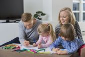 Parents with children drawing together at home