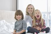 Portrait of happy mother with children in bedroom