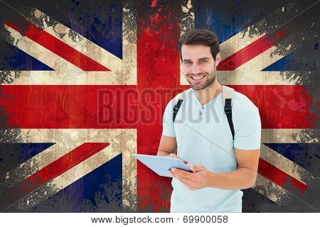 Student using tablet pc against union jack flag in grunge effect