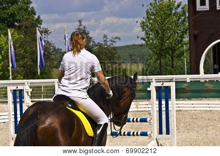 Female horse rider at showjumping event.