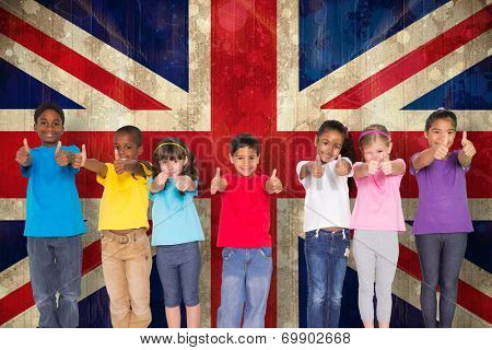 Elementary pupils smiling showing thumbs up against union jack flag in grunge effect